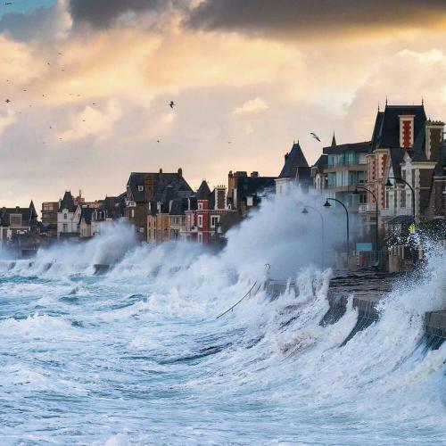 Прибой, морская волна накрывает прибрежную улицу